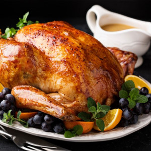Roasted whole chicken garnished with fruits and gravy, a famous American cuisine.