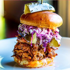 Pulled pork sandwich with cabbage topped with pickles is a sample of comfort food in Las Vegas.