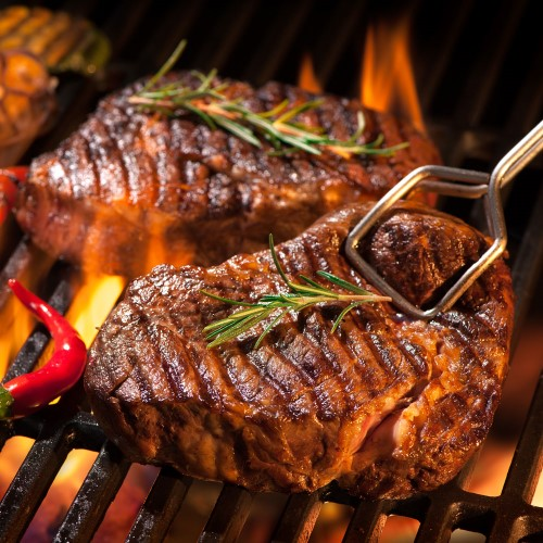 Steak being barbecued over a grill in a Strip restaurant