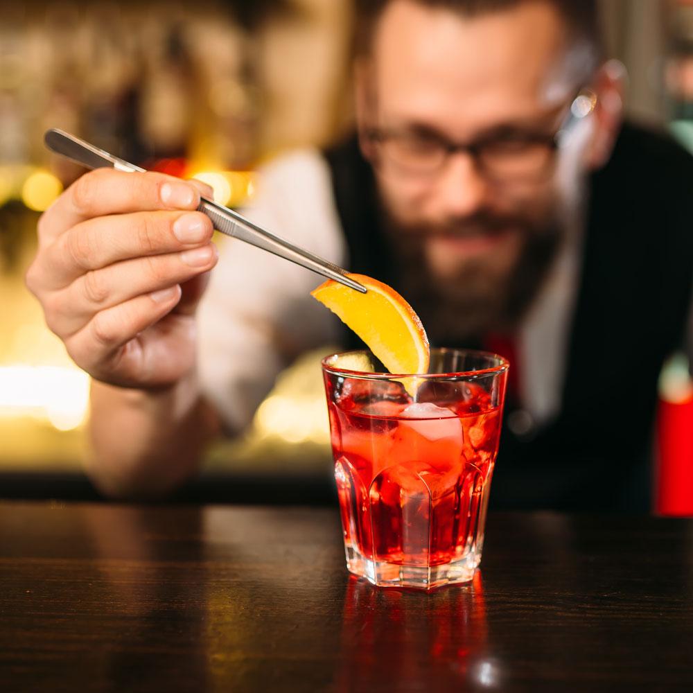 Bartender putting a slice of orange on a cocktail drink