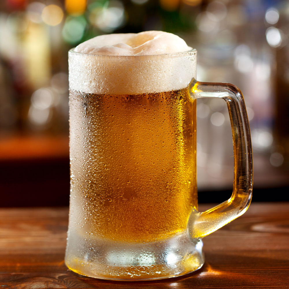 Cold beer in a clear mug on a bar table
