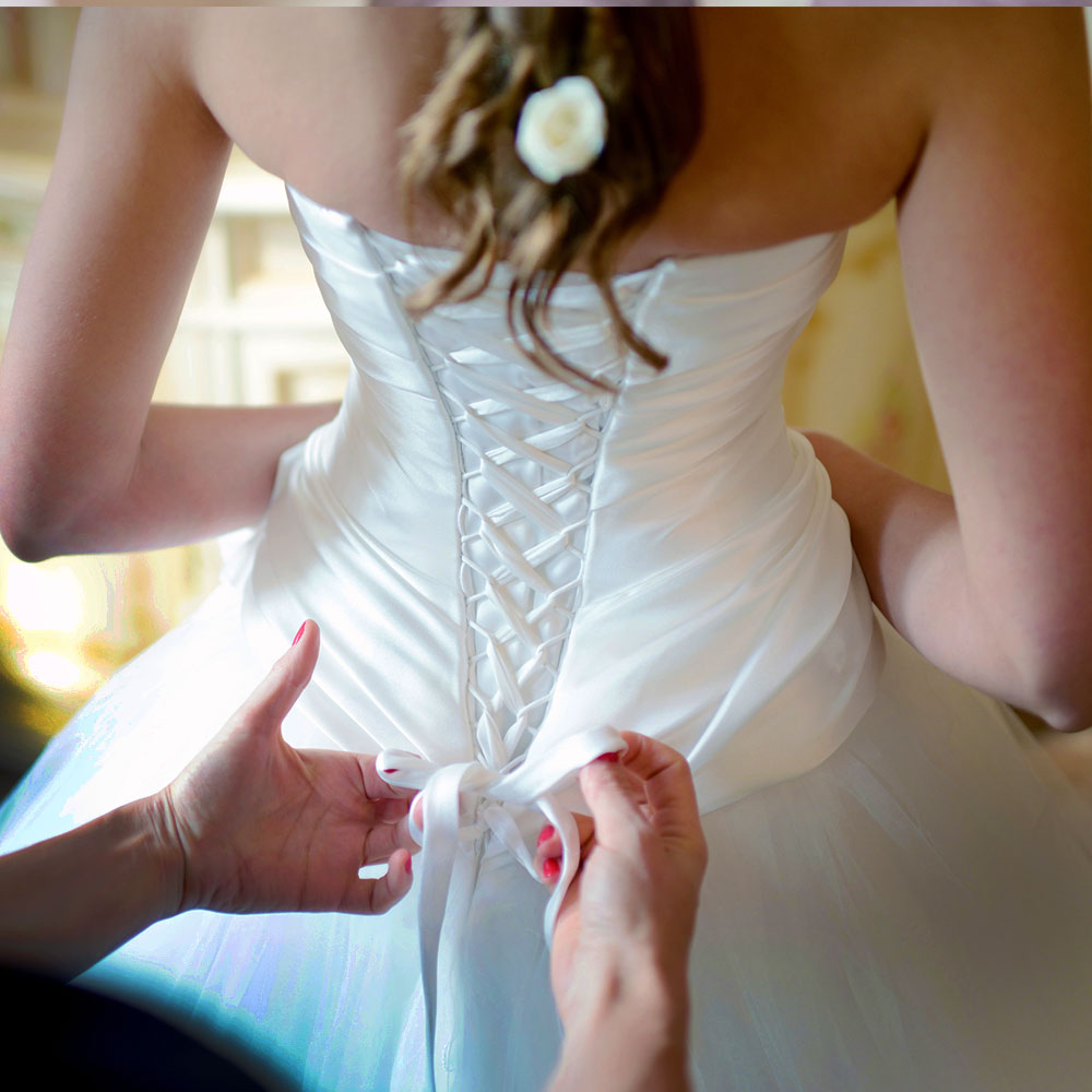 Soon to be bride fitting her wedding gown in a bridal shop.