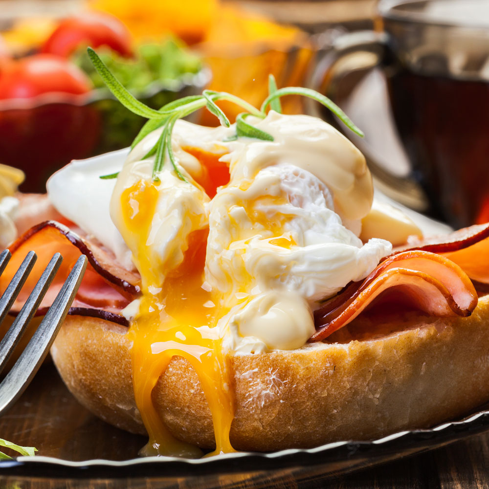 A set of food served for brunch that includes bread toast with cold cuts, eggs, and vegetables.