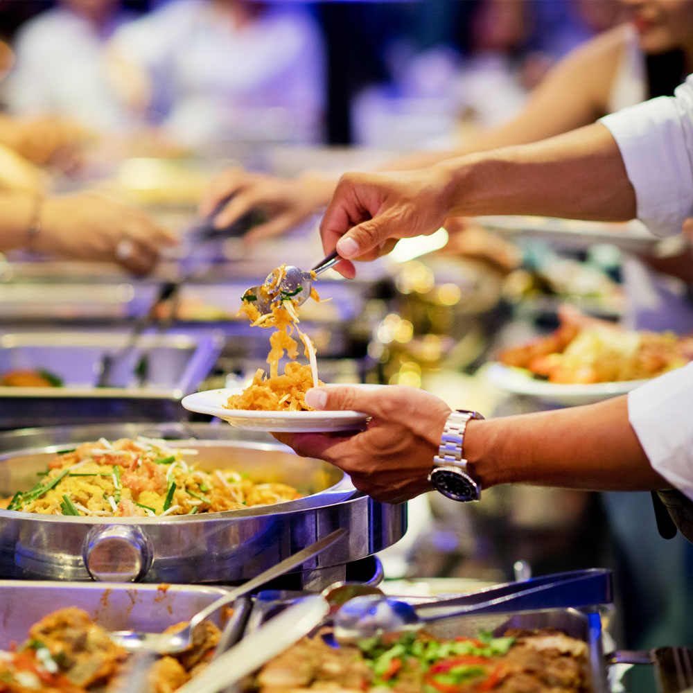 Chafing Dishes filled with food lined in a buffet table for catering.