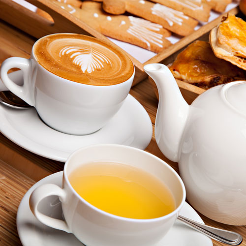 Cups filled with hot coffee and tea on a wooden table at a cafe