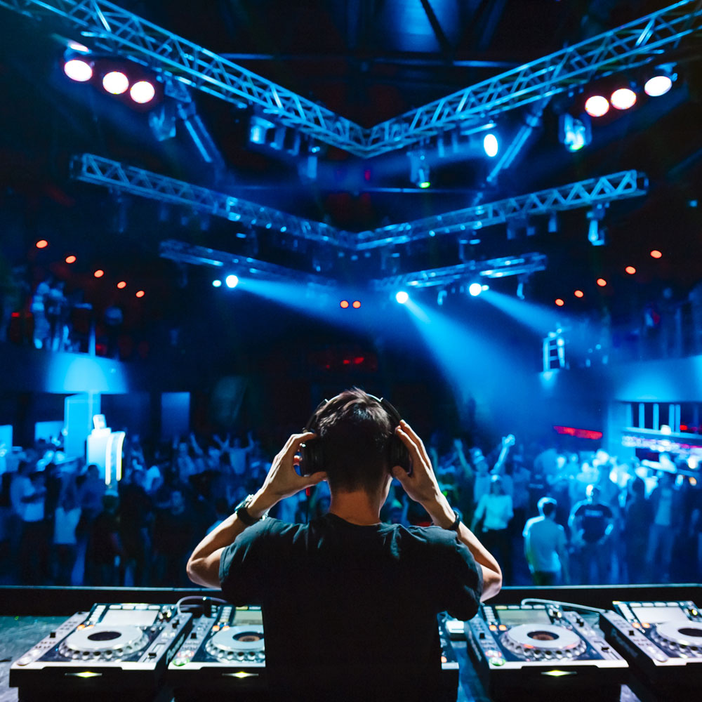 DJ holding his headphones playing music for the dancing crowd in a club