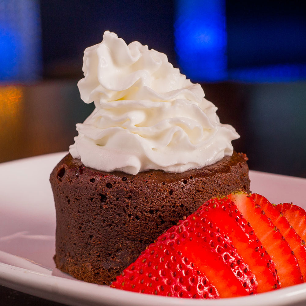 Chocolate Cake topped with whip cream and sliced strawberry is a famous food served for dessert.