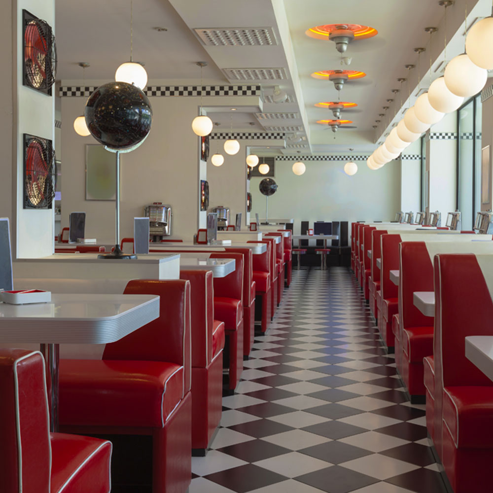 Dining area of a diner in Las Vegas Strip, with red couch and white tables where food is served