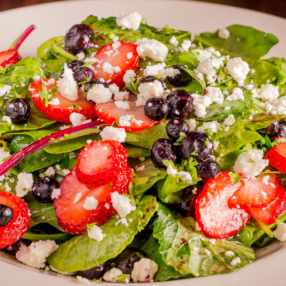 A dish of a healthy food made from green leafy vegetables with sliced strawberry, cheese, and black olives.