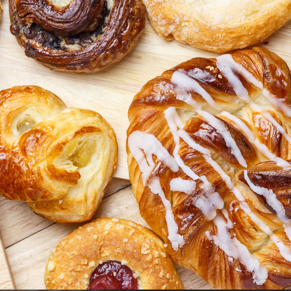 Freshly baked croissants, cinnamon rolls and assorted breads available in pastry or bakery shop.
