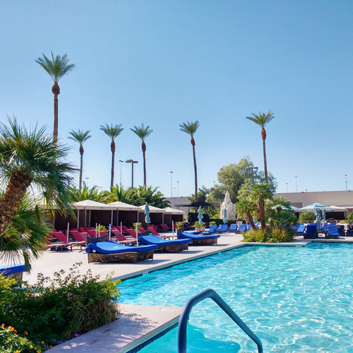 Pool area of a resort in Canyon Gate with poolside beds and tables
