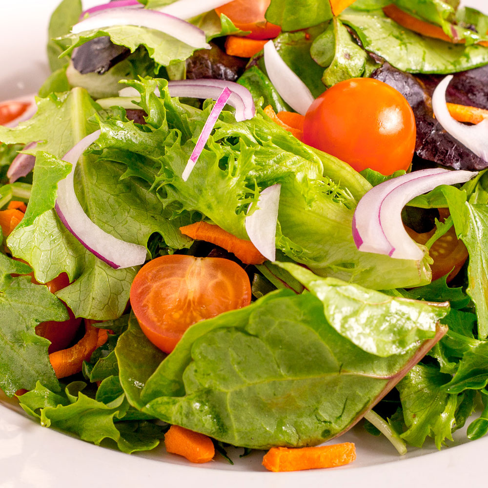 Healthier food option of kale, spinach, lettuce, tomatoes and red onion salad.