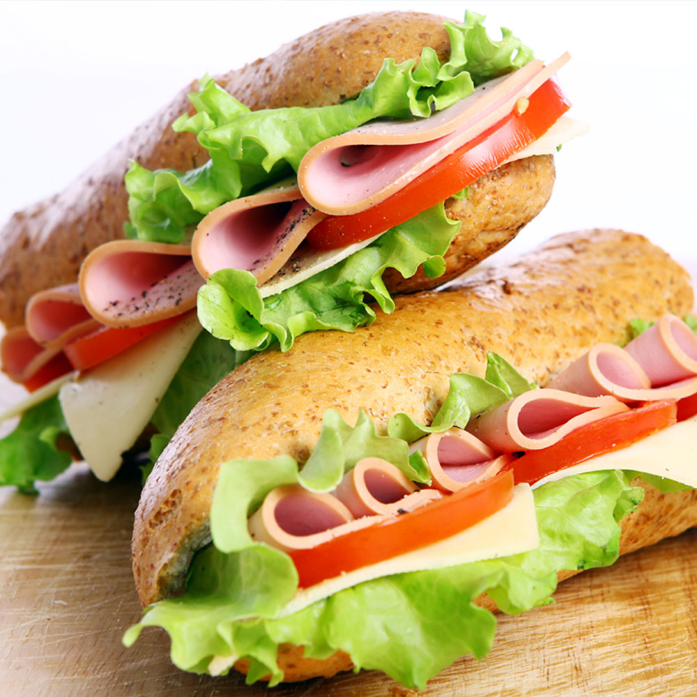 Deli sandwiches made up of subway buns with ham, tomato, lettuce and cheese.