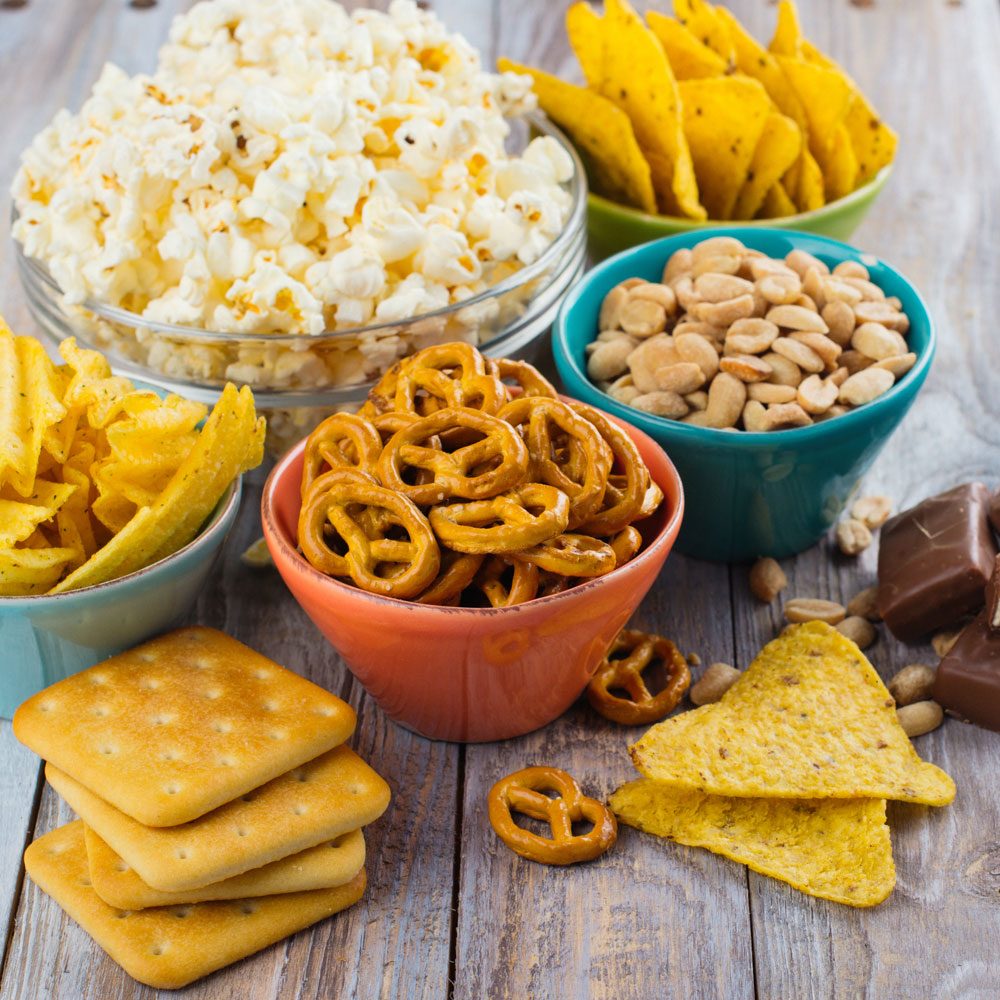 Biscuits, bowl of pretzels, bowl of popcorn and some chocolate bars consumed as snacks.