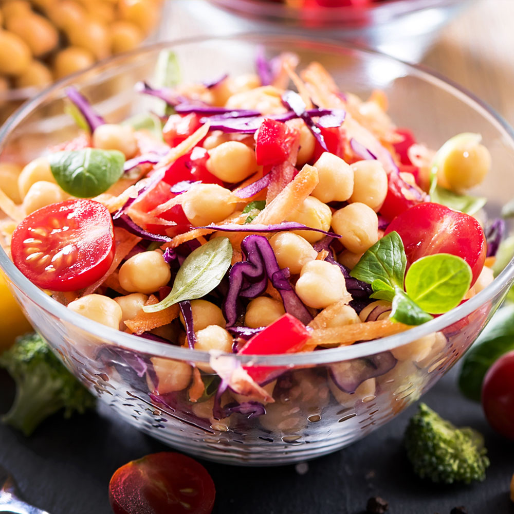 Vegan foods consisting of beans, vegetables and grains all mixed in a glass bowl.