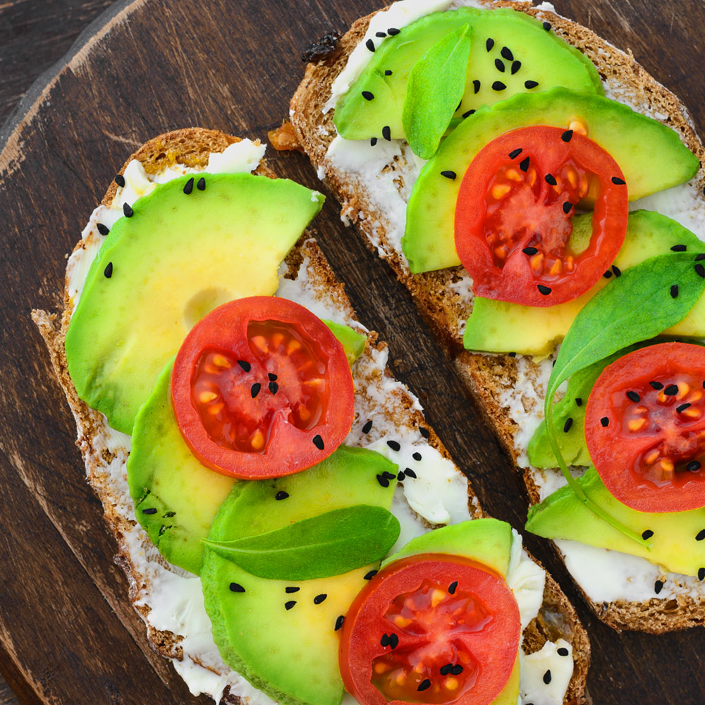 The vegetarian set meal consists of slices of wheat bread with cream, avocado, tomato, and sesame seeds.