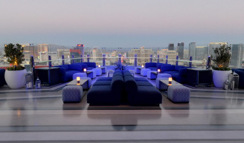 Chairs, tables & couch in the patio of APEX Social Club, overlooking the city of Las Vegas